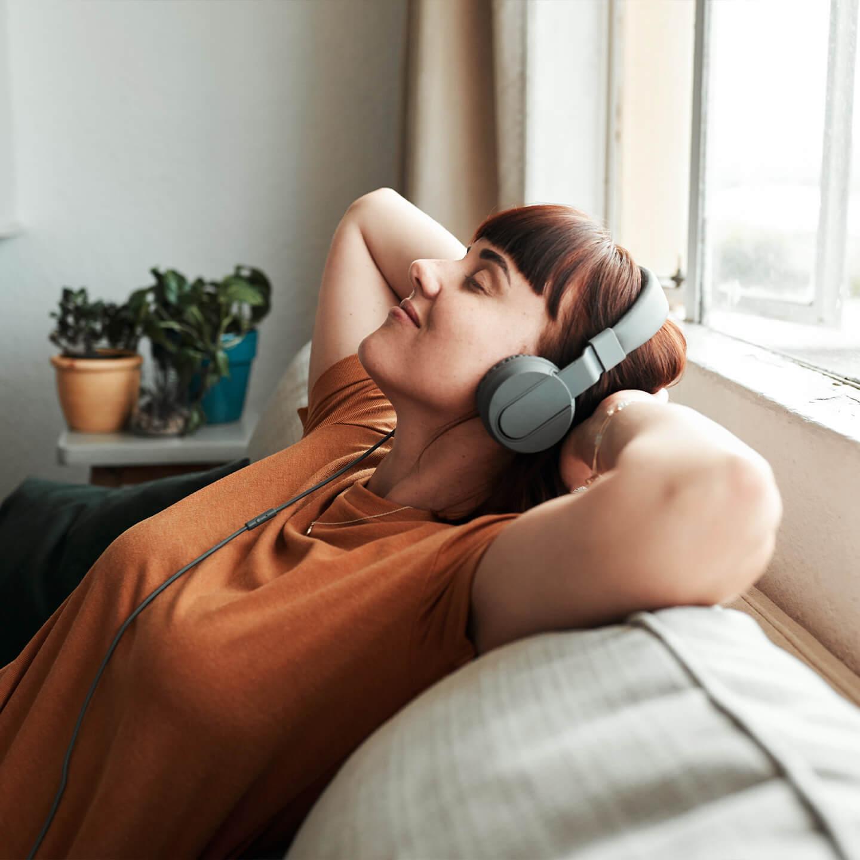 Entspannte Frau auf Sofa mit Kopfhörern