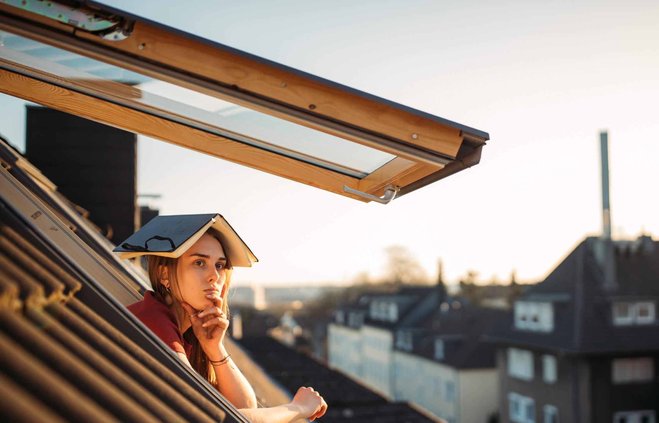 Frau schaut nachdenklich aus dem Fenster