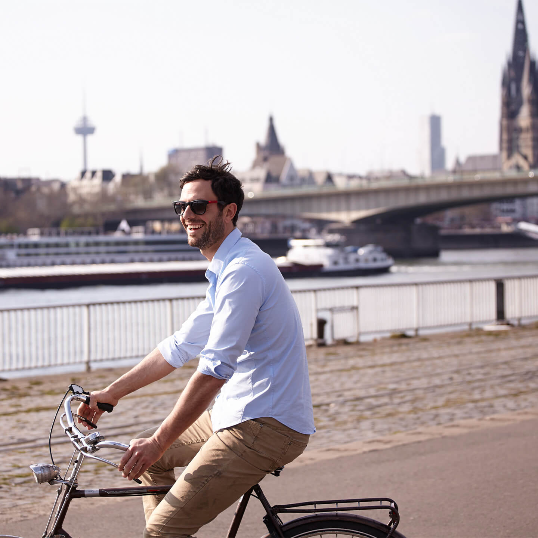 Mann auf Fahrrad am Rhein